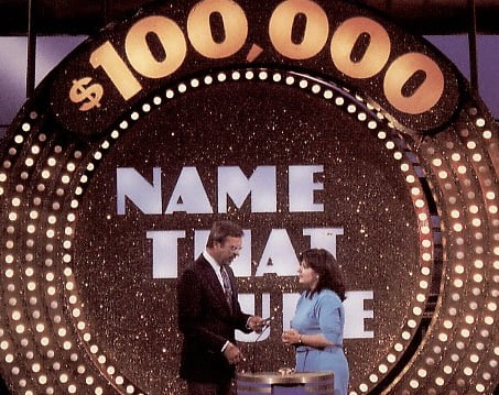 Image of host and contestant on Name That Tune television game show.